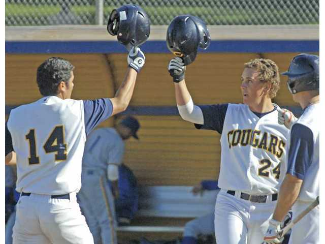 College of the Canyons baseball players Hugo Hernandez (14) and Trevor Bloom (24) click helmets after scoring a run earlier this season.