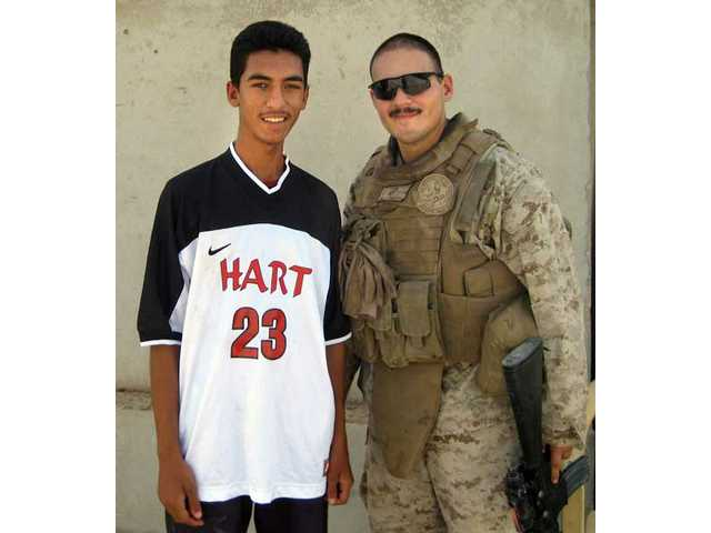 Ernesto Trevizo, right, poses in Iraq with an Iraqi teen wearing a Hart High School soccer uniform.