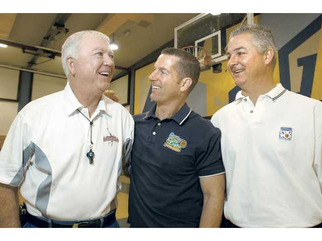 Bill White, left, and sons Dave, center, and Deron pose together at Castaic Middle School on Saturday. The trio has more than 70 years of experience refereeing basketball games.