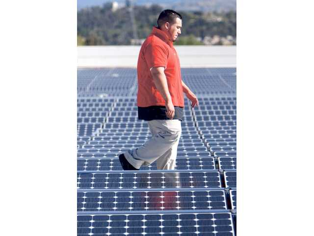 Cesar Lopez, 25, walks by solar panels which were installed on the roof of the JCPenney Store located at the Valencia Town Center on Monday. The store is one of a few nationwide participating in a pilot program to test the solar panels' efficacy.