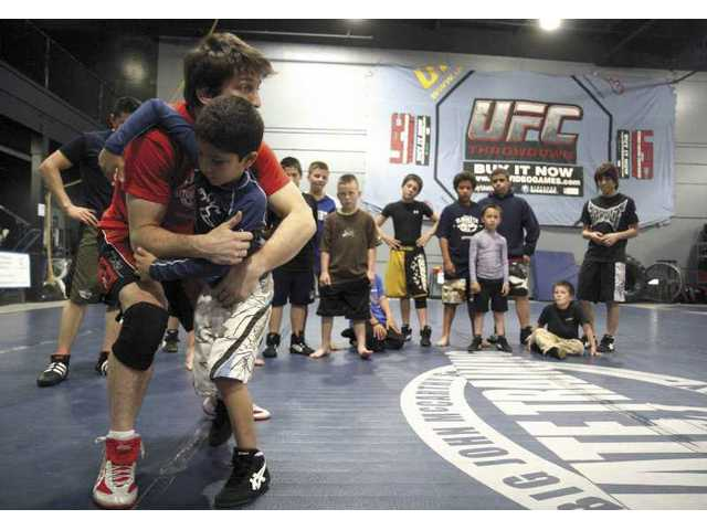 Wrestling instructor Brian Peterson demonstrates a move to 6-year old Sonny Santana at Big John McCarthy's Ultimate Training academy Tuesday in Valencia. BJMUTA is one of the few places in the area where kids can learn about the sport.