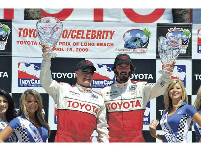 Al Unser, Jr., left, and Keanu Reeves celebrate their respective Pro/ Celebrity Race victories last year.