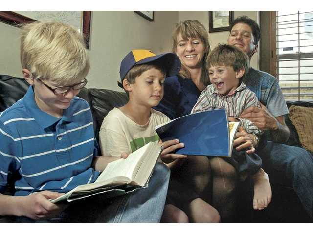 The Solomon family has been totally transformed by Adam's progress through Hardy Brain Training. Adam, left, now loves to read Harry Potter to Eric, 7, David, 3, mom Dianne and dad, Martin.