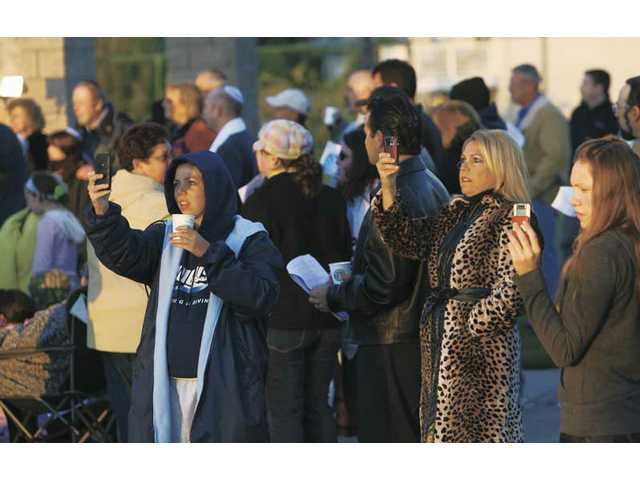 Worshippers snap photos of the sunrise Wednesday at the start of Temple Beth Ami's special service, during which they recited a collection of Psalms and traditional prayers.