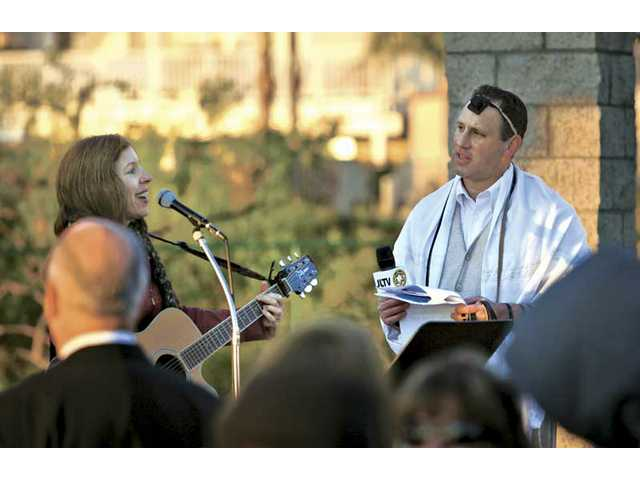 Temple Beth Ami's Rabbi Mark Blazer looks on Wednesday while Castaic musician Wendy Hersh leads the congregation in singing during the synagogue's sunrise Birkat Hachamah service.