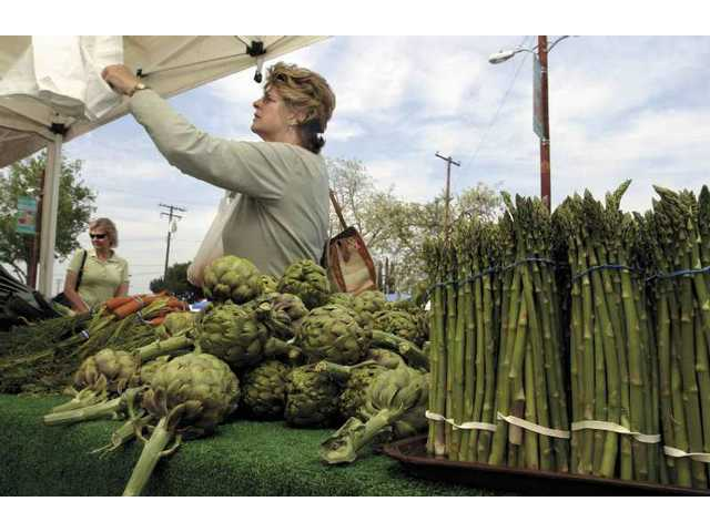 Shoppers scrutinize the produce at the Farmers' Market in photo from April 2007. Whole Foods Market in Valencia has partnered with the city of Santa Clarita to become a co-sponsor of the Farmers' Market in downtown Newhall, which reopens today.