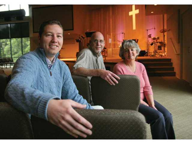 Senior pastor Steve Jackson, left, and one of the church's founding families, Mitch and Sheri McDiffett, sit inside the Faith Commuity Church. The church turned 25 on Easter Sunday.