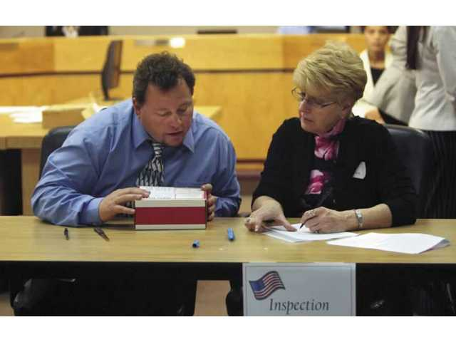 Anthony Calderon and Arlene Anthony count votes at City Hall on Tuesday night following the closing of the polls. Voter turnout in Santa Clarita was about 16 percent of registered voters.