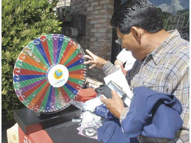 Valencia Liquor customer Carlos Vasquez spins the wheel for free gifts as part of a celebration for the store being named California Lottery's Retailer of the Month on Wednesday.