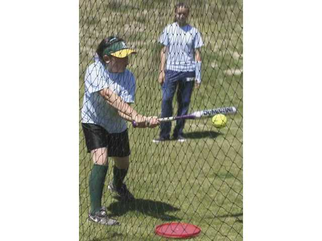 Third-grader Janelle Sheehan works on her swing with Saugus High softball player Michelle White.