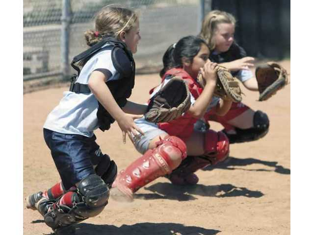 Tracy Adams, left, Vanessa Leyva, middle, and Kasey Herrington practice blocking pitches in the dirt during the Saugus High softball team's clinic on Thursday.