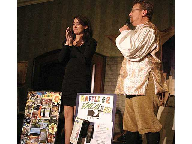 Event Chairwoman Leslie Garman and emcee TimBen Boydston hawk raffle items at the fifth annual Midwinter Madrigal Feast held at the Hyatt Regency Valencia.