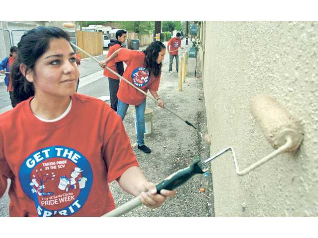 Rosa Rodriguez, 18, left, and Jennifer Perez join a group of teens from the Newhall Community Center in painting over graffiti in Newhall as part of a Santa Clarita Pride Week event on Saturday.