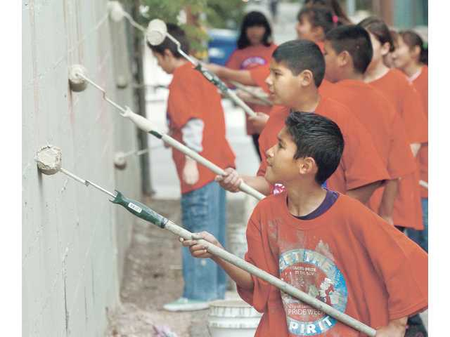 Luis Guerrero, 11, front, and Jesus Hernandez, 10, of the Future Leaders group at the Newhall Community Center, help paint over graffiti in Newhall as part of Santa Clarita Pride Week on Saturday.