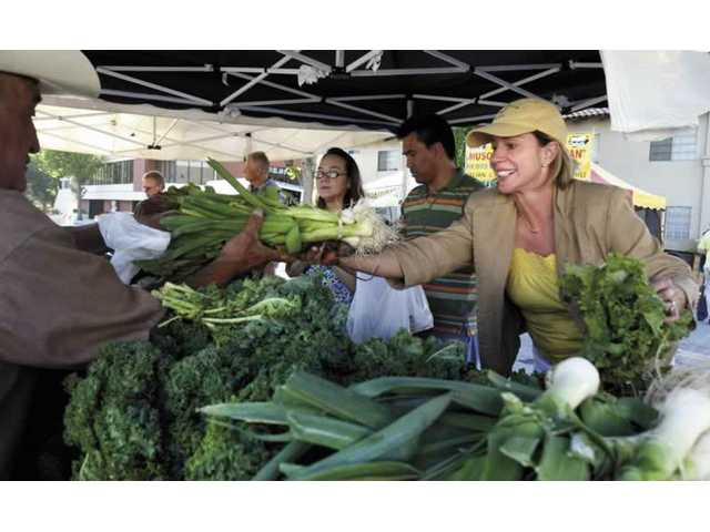 Diego Pena from Arriola Farms in Oxnard hands fresh vegetables to Katin Mortellaro from Santa Clarita on Thursday afternoon at the Newhall Farmers' Market. The market opened for the summer on Thursday.