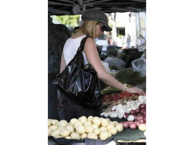 Jenn Douglas, of Valencia, checks out produce sold at the Newhall Farmer's Market on Thursday.