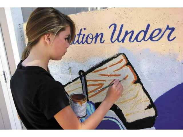 Fifteen-year-old Saugus High freshman Shannon Hoofman touches up the Bicentennial mural at Friendly Valley on Friday. She spent her spring break refurbishing the more than 30-year-old mural, which the elements had faded.