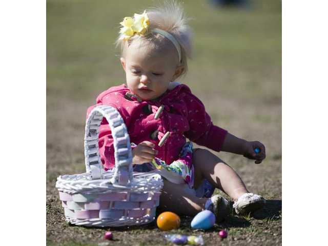One-year-old Mackenzie Mueller, of Saugus, collects eggs during her first egg hunt at Central Park on Saturday morning.