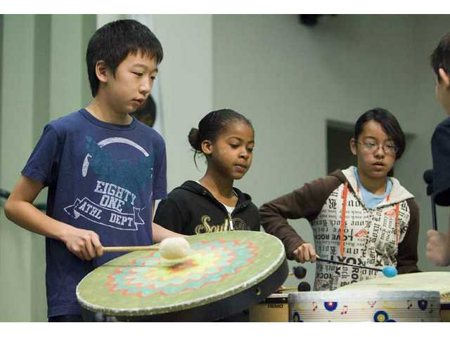 Fifth-grader Daniel Kim plays the skin drum during the final performance of the school's multi-week arts and literacy program called Arts for Learning Lessons at Leona Cox Community School on March 3.
