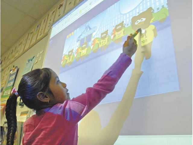 McGrath Elementary School first-grader Esmerala Morales puts letters in order using the computer smart board's projected image as she works on her language arts skills Wednesday.