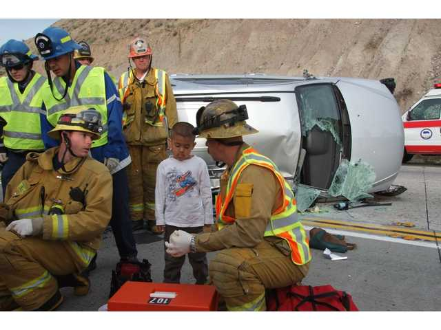 L.A. County firefighters/paramedics talk with a four-year-old boy who suffered only minor injuries when a minivan driven by his mother collided with the center divider and rolled over on Highway 14 this morning.