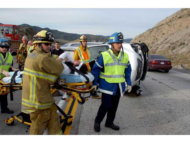 L.A. County firefighters/paramedics wheel a seriously injured driver on Highway 14 to a waiting helicopter, which flew him to a local hospital this morning. The driver crashed into the rear of a fire truck that had responded to a minivan rollover.