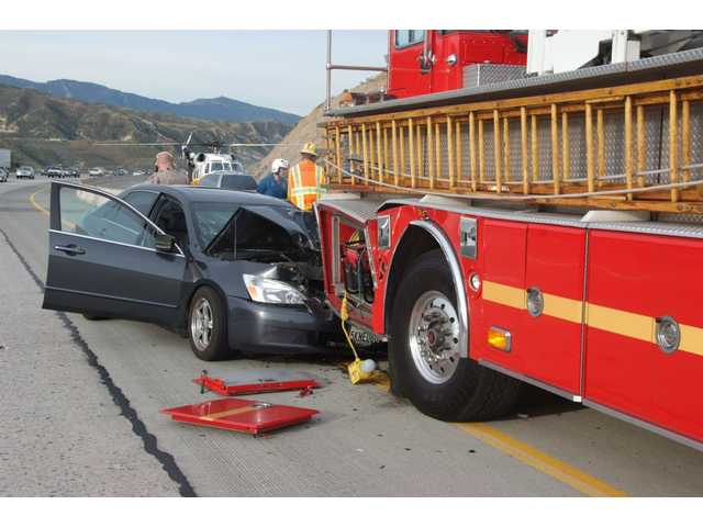 A man driving a Honda Accord was seriously injured on Highway 14 this morning when his car crashed into the rear end of an engine from L.A. County Fire Station 104, as firefighters/paramedics were treatinga woman and her two children of minor injuriessuffered whenthe minivan she was driving collided with the center divider and rolled over.
