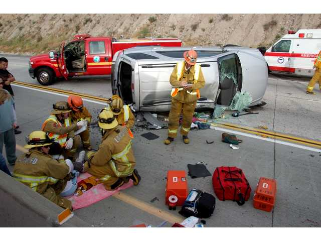 L.A. County firefighters/paramedics treat a woman and her two children, who suffered only minor injuries when the minivan she was driving collided with the center divider and rolled over on Highway 14 this morning.