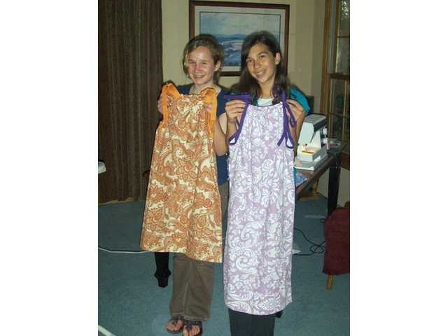 Placerita Junior High School seventh-graders Shelly Peer and Michelle Kummer show off their newly made dresses for the Little Dresses for Africa project. The girls hand-made a total of 15 dresses.