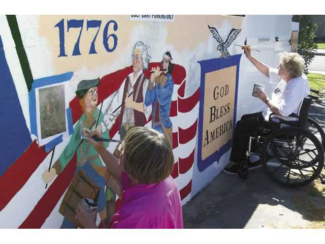 Members of the Santa Clarita Artists Association work Friday on restoring the Bicentennial mural.