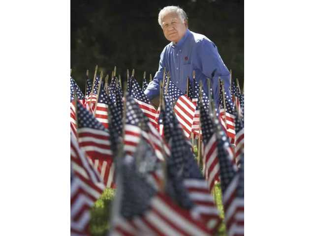 Retired Vietnam era serviceman, Alex Reza, stand by the American Flags on his front yard. Each flag represents 10 casualties in the Iraq war.