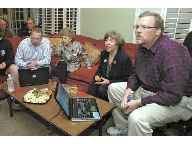 City Council candidates Marsha McLean, second from right, and Frank Ferry, right, watch the results on a big-screen TV on Tuesday. The two incumbents were joined by Ferry's brother Pete, far left, and friend Margot Arden.