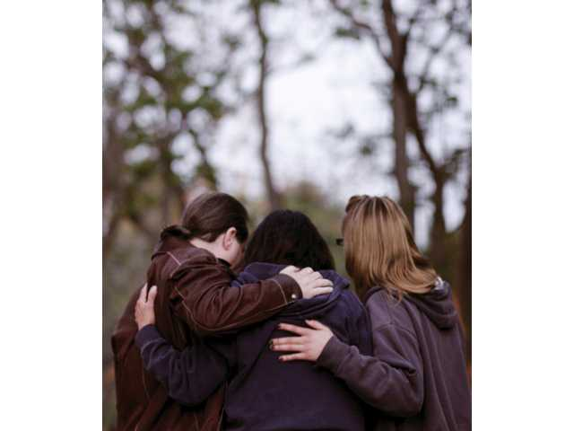 Cary Quashen, left, of ACTION, embraces Shirley Shields, center, of Newhall, and her daughter Danielle Shields, during Monday's Evening of Remembrance in the Youth Grove at Central Park in Saugus.