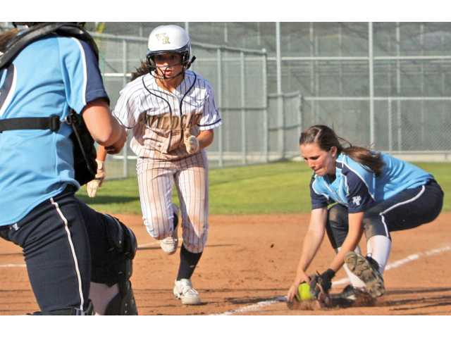 West Ranch's Kylie Sorenson, center, charges home toward Saugus catcher Ashley Butera, left, in the seventh inning as Saugus third baseman Karlee Bickford fields a ground ball Tuesday at West Ranch High.