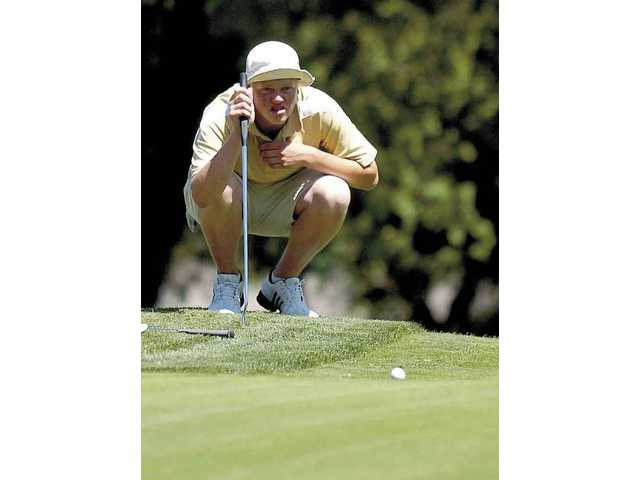 J.J. Holen of West Ranch High lines up his putt on the fifth hole at Valencia Country Club Monday afternoon during the fourth Foothill League match.