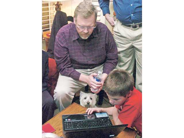 City Councilman Frank Ferry, seated, watches election results Tuesday with David Ender, 11, and terrier, Abby, at an election night party in Saugus.