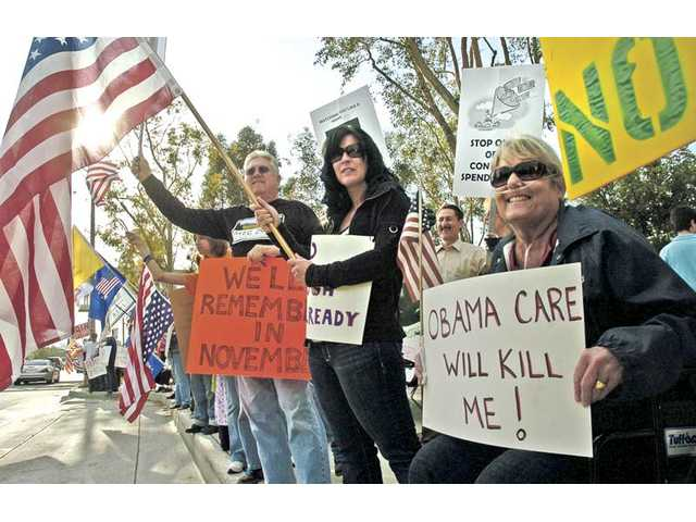 From left, Bill Gausnell, Lisa Digiacomo, and Kathy Gabel join hundreds of participants at a tea party rally that lined both sides of Valencia Blvd. near City Hall on Thursday.