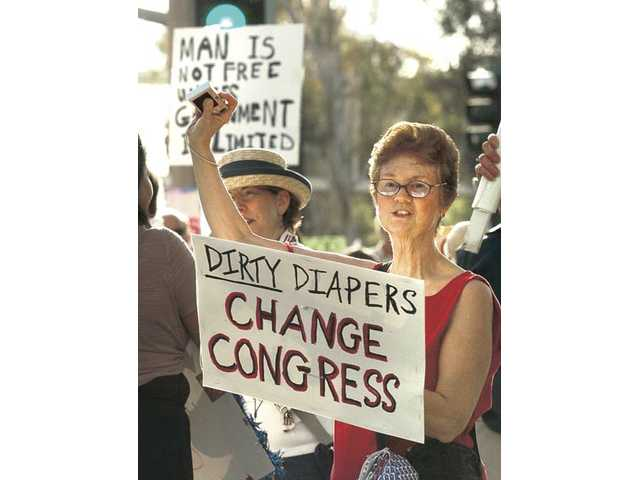 Sylvia Cole of Canyon Country waves her homemade sign as she joins hundreds of participants that lined Valencia Blvd. at a tea party rally held near City Hall on Thursday.