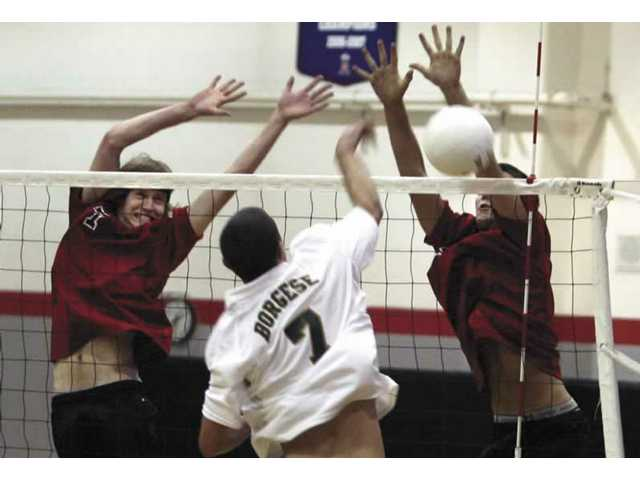 Hart High's Shane Siezega, left, slams a kill over the net as Brent Borgese of Canyon (7) attempts to block the kill. The Indians won the mtach in five games and Siezega finished the match with 20 kills.