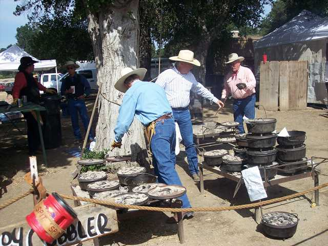 The Cowboy Cultural Committee cooks tend to the group's famous peach cobbler.