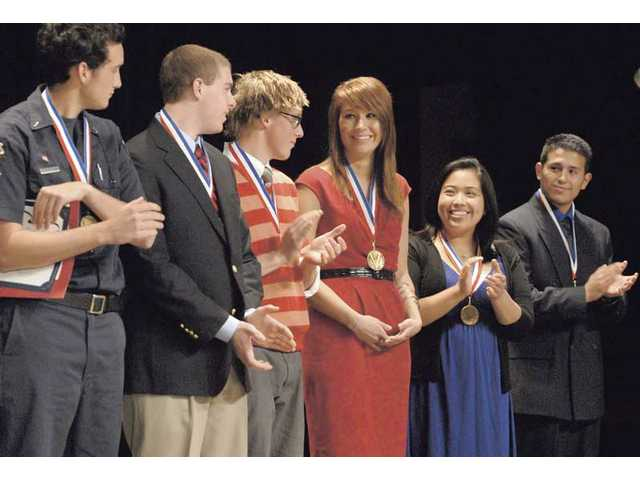 Ava Bardsley, center, is announced Outstanding ROP Student of the Year as she stands with Outstanding Student gold medal winners, from left, Phillip Suarez, Thomas Beckett, Elliot Adair, Carol Chavez, and Anthony Trejo at the Road Of Prosparity,  ROP Student Award program at Rio Norte Junior High on Tuesday.