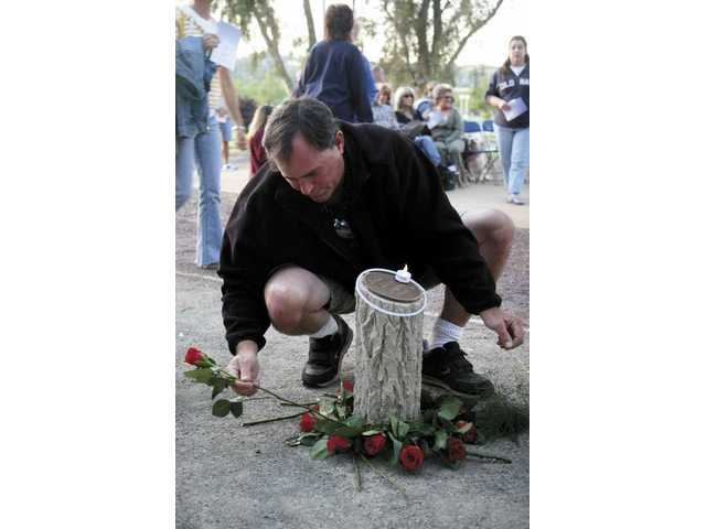 Frank Diacri of Valencia arranges roses around the memorial to his best friend's son, Zachary Russel Legreid, forever 15.