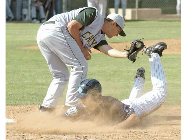 Saugus' Tylor Klipfel, right, slides under Canyon first baseman Alex Banta's tag on Friday at Saugus High School.