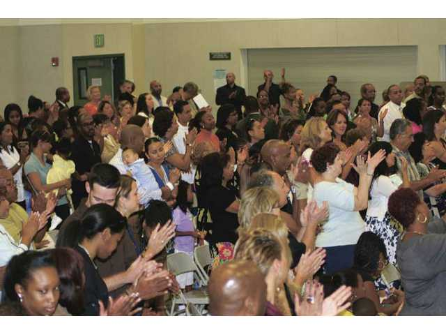Valencia Christian Center antendees enjoy the praise and worship during a service at Pico Canyon Elementary School's multipurpose room.