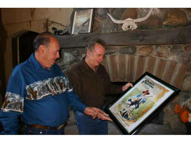 Melody Ranch Motion Picture Studio owners Andre and his brother Renaud Veluzat, standing before the huge fireplace in the ranch's production office, check out the 2008 Cowboy Festival poster art created by past Western Walk of Stars inductee Buck Taylor.