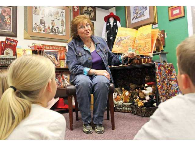 Janet Squires reads her children's book to eager listeners at the OutWest store in Newhall.