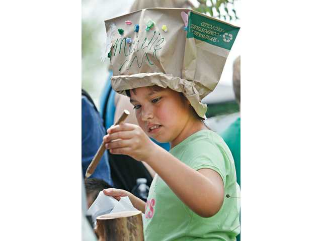 Michelle Marquez, 7, of Canyon Country, sports a paper bag hat made for her by the YMCA artists during Santa Clarita's Earth/Arbor Day.