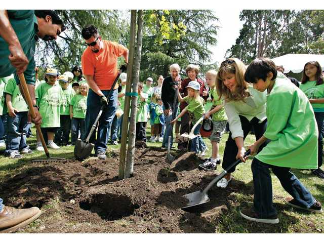 Santa Clarita Mayor Laurene Weste, background, with Councilmember Marsha McLean watch McLean's grandchildren, Ciara and Aidan Wilkins dig mulch to start the city's Earth Arbor Day event by planting a small oak tree. Councilmember Laurie Ender, third from right, helps Carl Ramirez dig.