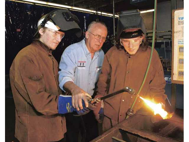 Welding instructor Jack Compton, center,  works with brothers who are Boy Scouts, Bleys (cq) and Brand Foust at COC welding class on Thursday.
