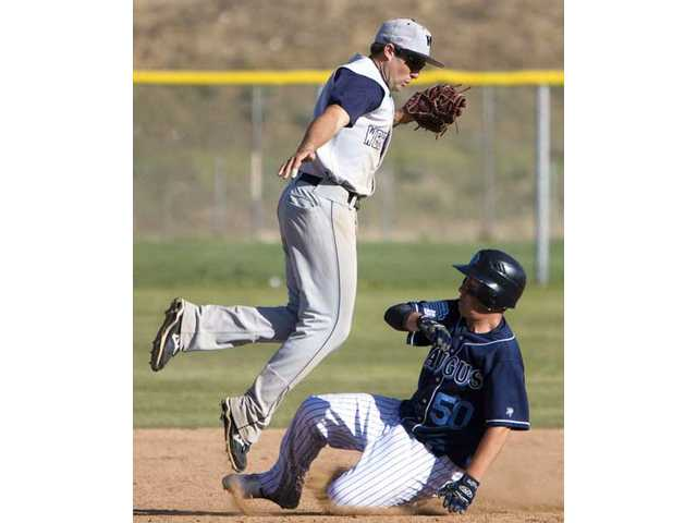 West Ranch's Cal Vogelsang, left, leaps out of the way of a sliding Michael Soucy, of Saugus, Friday.